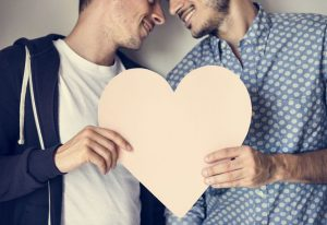 Two men looking at each other and holding a cut out heart shape