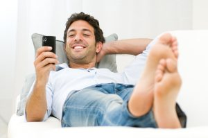 Young smiling man laying on the sofa messaging on his mobile phone at home.